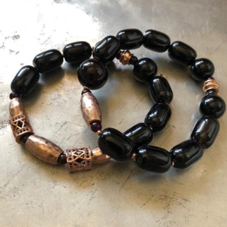 دستبند دو حلقه ای از سنگ انیکس بشکه ای که در لا به لای این سنگ ها از تزیینات رزگلد استفاده شده است .