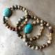 دستبند سه حلقه ای از سنگ جاسپر خاکی رنگ که دو حلقه از این دستیندها به سنگ فیروزه رودخانه ای متصلند . در لا به لای این سنگ ها از سنگ حدید نیز استفاده شده است .