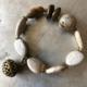 دستبند کشی از سنگ جاسپر اشکی و گرد و براق های برنزی