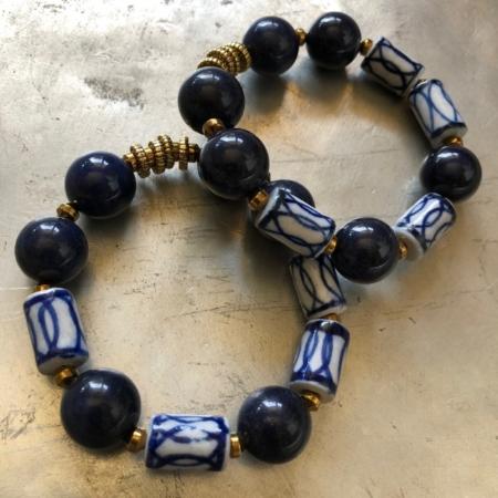 دستبند دو حلقه ای از سنگ عقیق سورمه ای و سرامیک که در لا به لای این سنگ ها از سنگ حدید و تزیینات برنچی استفاده شده است .