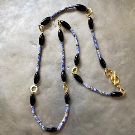 گردنبندی بلند و ساده از سنگ سودالیت لوله ای با جدا کننده های حلقه ای از جنس برنج که با سنگ انیکس دوکی شکل ادغام شده است.