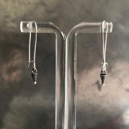 گوشواره ای ساده و سبک از فلز نقره. پایه این گوشواره بلند بوده و آویز آن از جنس نقره و به شکل نوک پیکان است.
