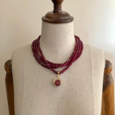 گردنبندی از چهار رشته سنگ عقیق سرخ تراشدار که به آویزی جذاب از حلقه دو رو که یک روی آن سنگ عقیق و یک روی آن سنگ فیروزه است.