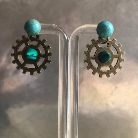 گوشواره ای ساده و شیک از سنگ فیروزه نیمکره که به پایه میخی چسبیده و آویزی به سبک مدرن و صنعتی از جنس فلز آلیاژ به آن متصل است .