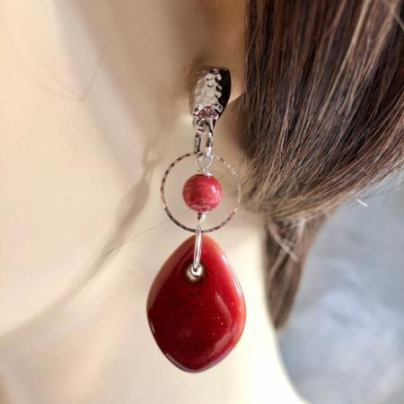 گوشواره ای با سبکی مدرن از سرامیک اشکی سرخ که به حلقه ای استیل و پایه ای با روکش نقره متصل است.